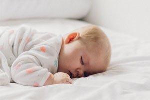 Ein süßes Baby der auf einem Bett, mit Metallfreie Lattenroste, schläft.