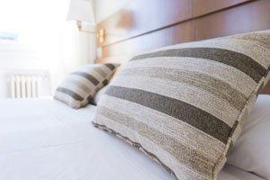 Weißes Bett auf dem zwei gestreifte Kissen liegen.