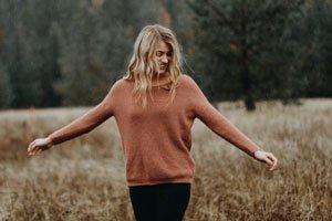 Eine Frau im Orange-Pinken Pullover, Lächelnd, auf einem Feld.