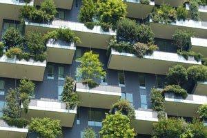Eine Hausfassade mit vielen Balkons. Auf allen Balkons sind Bäume angepflanzt.